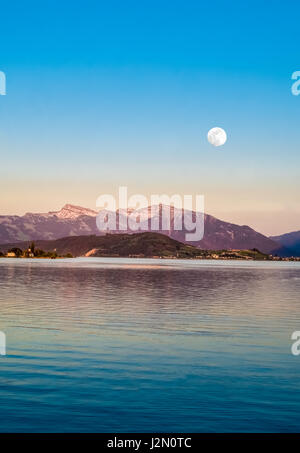 Full moon over the upper lake Zurich (Obersee) at dusk on a clear spring night, Rapperswil, Sankt Gallen, Switzerland - Stock Photo