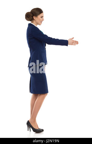 Young woman in blue formalwear and high heels, standing and giving hand for a handshake. Side view. Full length - Stock Photo