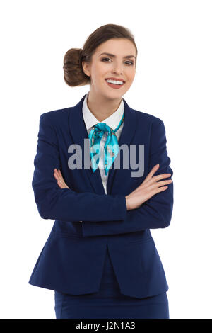 Smiling beautiful woman in blue suit and turquoise scarf posing with arms crossed and looking at camera. Waist up - Stock Photo