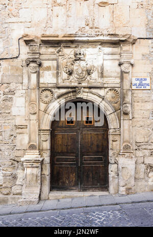 Wooden double doors and Jesuit coat of arms on the old Colegio de los Jesuitas, a historic building in the old medieval - Stock Photo