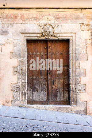 Old wooden double doors below a coat of arms on a historic building in the old medieval town of Cuenca, Castilla - Stock Photo