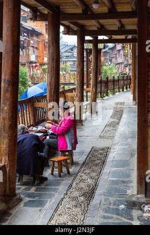 Zhaoxing, Guizhou, China, a Dong Minority Village.  Women Sewing in front of their House. - Stock Photo