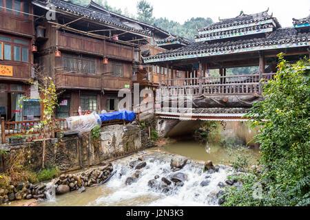 Zhaoxing, Guizhou, China, a Dong Minority Village.  Wind and Rain Bridge Crossing Small River Running through the - Stock Photo