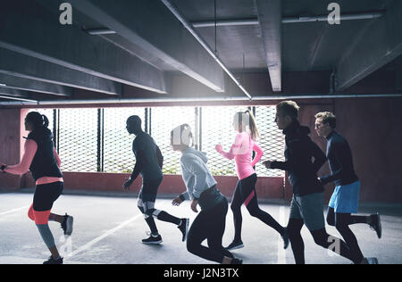 Group of active young friends urban running sprinting as a pack through an undercover commercial car park in a health - Stock Photo