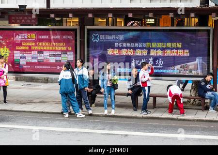 Kaili, Guizhou, China.  People Waiting at a City Bus Stop. - Stock Photo