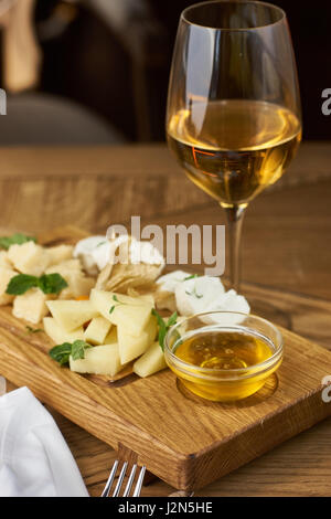 Cheese plate with honey and wine - Stock Photo