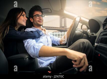 Woman and man hugging in car - Stock Photo