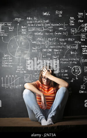 Depressed woman in front of chalkboard with notes - Stock Photo
