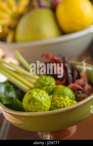 Thai and asian food ingredients in bowls, bergamots, dried chillis, lemons, limes, lemongrass, banana, pomelo, selective - Stock Photo