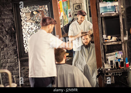 bearded man getting haircut by hairdresser while sitting in chair at barbershop - Stock Photo