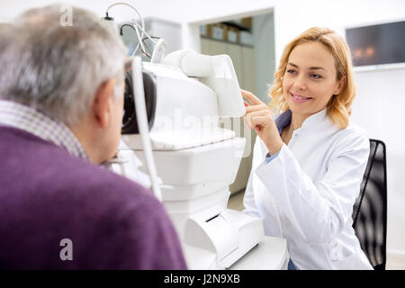 Young female eye doctor work with patient using eyes apparatus - Stock Photo