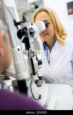 Female blond eyes doctor work with apparatus and check eyes to male patient - Stock Photo
