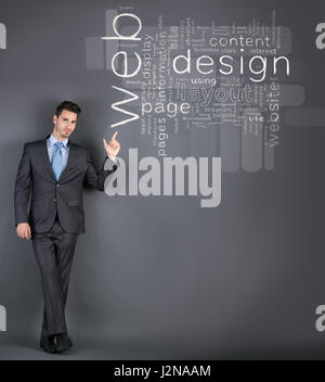 Businessman standing in front of a wall with web design terms and pointing on it - Stock Photo