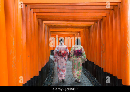Two geishas among red wooden Tori Gate at Fushimi Inari Shrine in Kyoto, Japan. Women wearing traditional japanese - Stock Photo