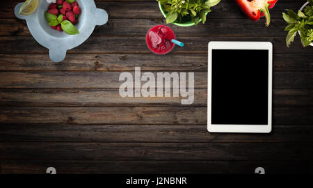 Red and green fruits, vegetables and herbs on wood background with customizable black screen device. Top view with - Stock Photo
