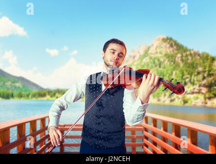 Male fiddler playing classical music on violin on wooden pier, lake and mountains on background. Violinist man with - Stock Photo