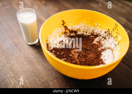 Bowl with dough, chocolate powder and glass of milk on wooden background. Sweet cake cooking. Homemade dessert ingredients - Stock Photo