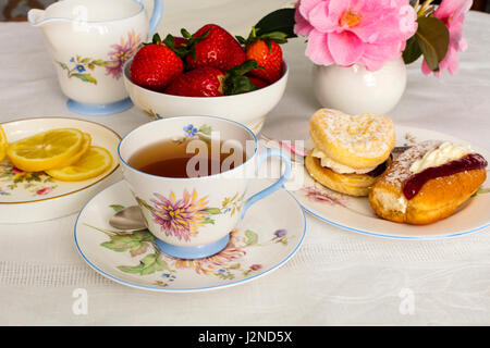 Cup of tea served in a vintage fine china tea cup with cream cakes. - Stock Photo