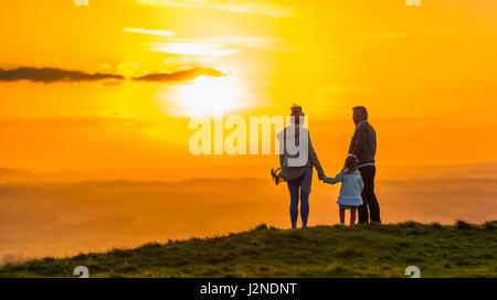 Small family standing on a hill watching the sunset while holding hands. Togetherness concept. Always concept. Closeness - Stock Photo