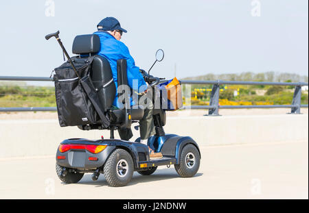 Elderly man on a path in an electric mobility scooter for disabled people. - Stock Photo