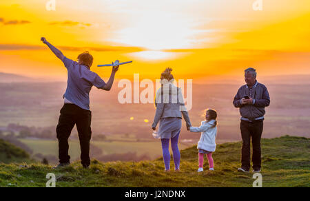 Loving family playing and enjoying good times on a hill close to sunset in the UK countryside. Spending time together. - Stock Photo