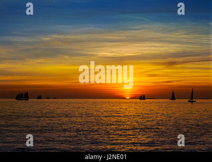 Sunset from Key West Florida with sail boats and a vivid color sky - Stock Photo