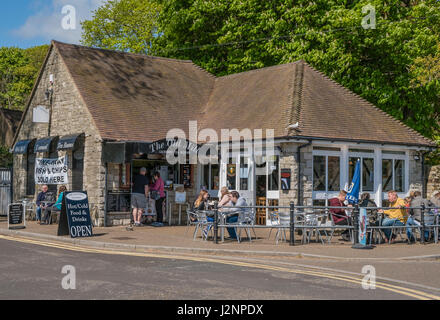 People sitting outside the Old Mill Tearooms and cafe, enjoying snacks and icecream at Christchurch Quay, Dorset, - Stock Photo