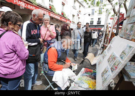 Tourists watch a painter at Place du Tertre in Montmartre on April 30, 2017 in Paris,France.