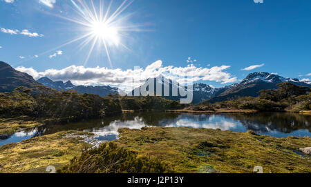 Sun shining on small mountain lake with reflection of a mountain chain, Key Summit Track, Fiordland National Park - Stock Photo