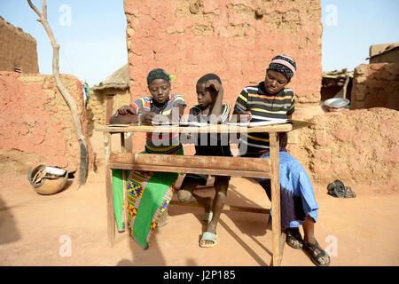 Teenage girls, 14 and 17 years, and boy, 9 years, doing homework, village Koungo, Plateau Central, Burkina Faso - Stock Photo