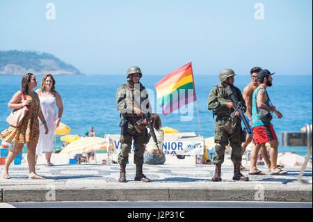 RIO DE JANEIRO - FEBRUARY 15, 2017: Two army soldiers in full camouflage uniforms stand with rifles on Ipanema Beach - Stock Photo