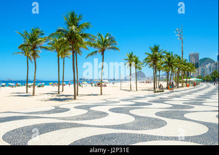Bright scenic morning view of Copacabana Beach with its iconic wave pattern boardwalk under blue skies - Stock Photo