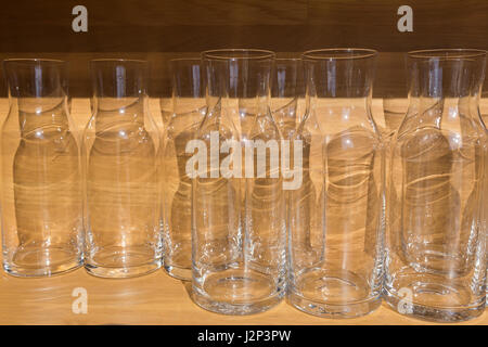 clear empty glass bottles or jugs on wood table placing agaist wood wall in morning light, selective focus - Stock Photo