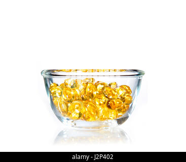 bright yellow soft Sacha Inchi gel pills in clear glass bowl on white background with copy space - Stock Photo