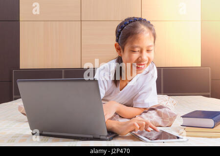 Happy Asian female teenager using technology, interacting with moblie computer tablet device in her bed - Stock Photo