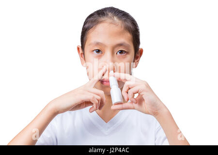 Teenage asian girl using nasal spray with one hand holding the spray bottle to her nose's left side and an index - Stock Photo
