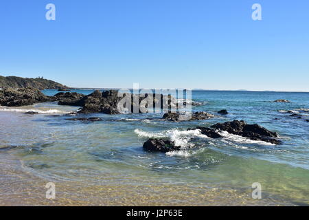 Sandy beach with dark rock formations on Nobby Beach in Port Macquarie. - Stock Photo