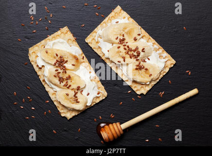 Dietary healthy breakfast. Sandwich crispy bread, ricotta, banana, honey and flax seeds on a black slate background - Stock Photo