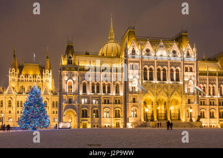 A Christmas tree and the Hungarian parliament building with snow - Stock Photo