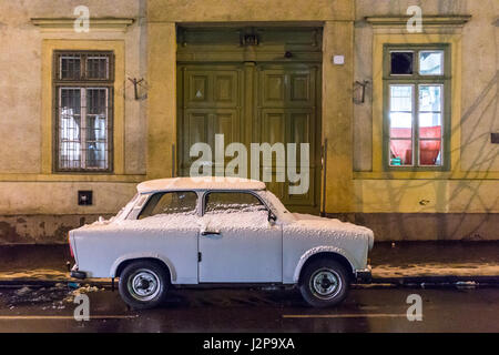 A trabant with snow on a street at night in Budapest - Stock Photo