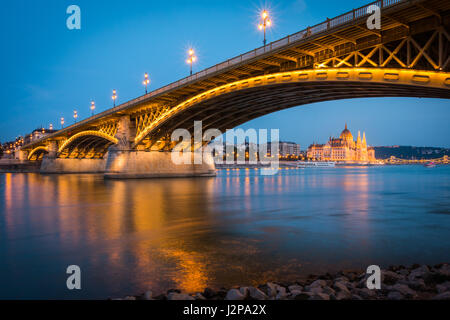 The Hungarian Parliament seen through an arch of the Margaret Bridge in Budapest - Stock Photo