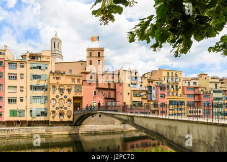 People walking on Pont d'en Gómez bridge over the River Onyar with the cathedral belltower towering over the old - Stock Photo