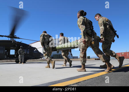 U.S. Soldiers in the CBRNE Leaders Course take a liter to a UH-60 Blackhawk helicopter during hot load training - Stock Photo