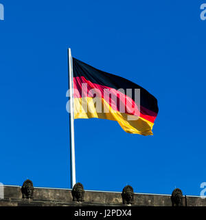 Silky flag of Germany flying in the wind.  German flag on the top of Reichstag building, Berlin, Germany - Stock Photo