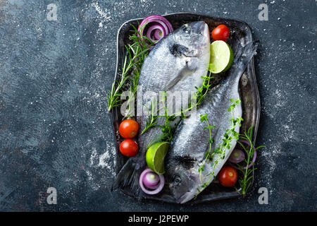 Fresh uncooked Dorado fish or sea bream with ingredients for cooking on dark background, top view - Stock Photo