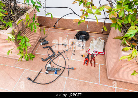 Luxurious copper drip irrigation system, with copper pipes. Micro irrigation system for pot plants on a terrace - Stock Photo