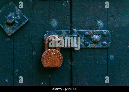 Old rusty padlock on wooden doors, old green destroyed door,safety, vintage - Stock Photo