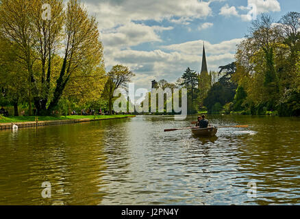 Stratford upon Avon and aAcouple enjoying a trip in a rowing boat on the River Avon, with Holy Trinity church spire - Stock Photo