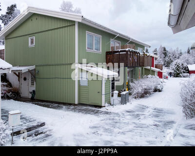 Exterior of typical swedish or scandinavian green wood semi-detached house covered in snow during winter  Model - Stock Photo