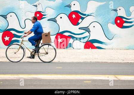 HAVANA - JUNE, 2011: A Cuban man on bicycle passes a colorful mural of propaganda featuring doves of peace emblazoned - Stock Photo